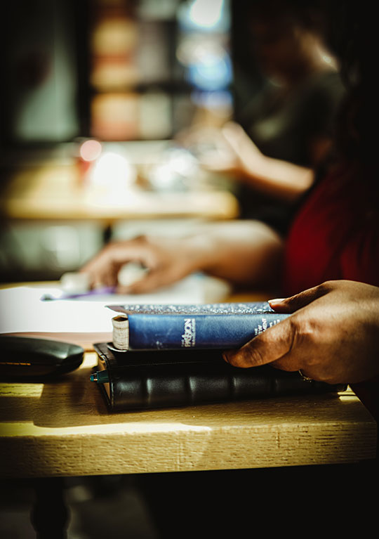 Bible and journal on a table in a coffee shop.